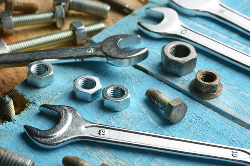 bolts and english wrenches on wooden table