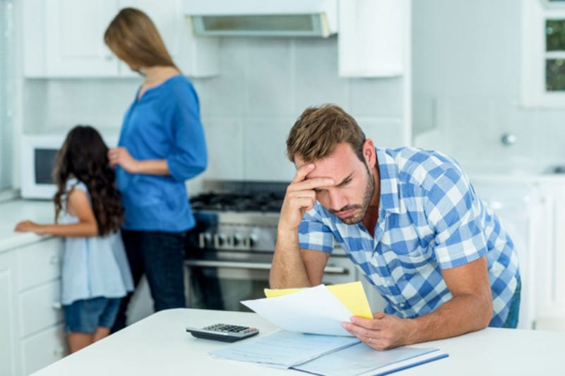 Worried Father Looking at Bills